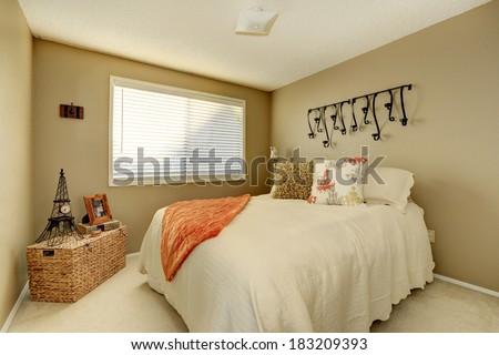 Gentle tones bedroom with ivory bedding, pillows and orange blanket. Room decorated with wicker chest and small eiffel tower