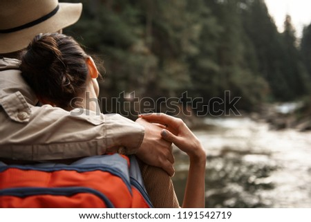 Gentle touch. Peaceful young woman gently touching the hand of her boyfriend while looking at the river flow and leaning her head on the shoulder of beloved man #1191542719