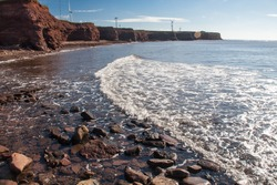 Gentle waves along PEI shoreline with wind turbines