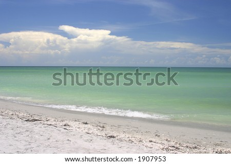 Gentle waves lap against a white sand beach on a sunny day
