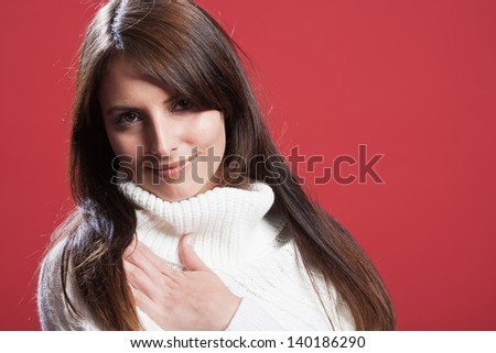Gentle woman in a polo neck pullover looking at the camera with a serene expression, isolated studio portrait on red