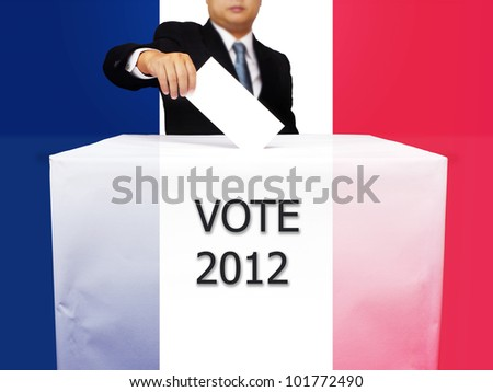 Gentleman hand putting a voting ballot in slot of white paper box and flag of France