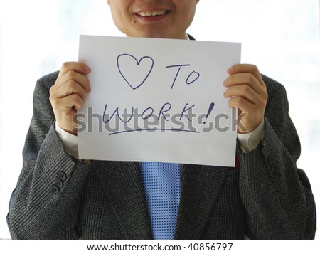 Gentleman holding a card saying Love to Work