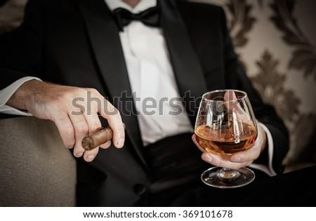 Gentleman holding glass of cognac and cigar