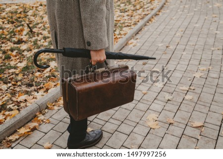 gentleman is waiting. A man in stylish shoes and a gray coat stands on a narrow alley of an autumn park. In the hand an umbrella-cane and a valise