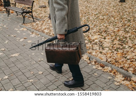gentleman's walk. A man in stylish shoes and a white coat walks along the narrow alley of the autumn park. In the hand an umbrella-cane and a valise