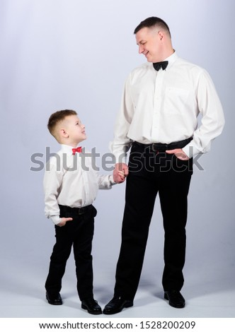 Gentleman upbringing. Visit theatre dress code. Father and son formal clothes outfit. Formal event. Grow up gentleman. Gentleman upbringing. Little son following fathers example of noble man.