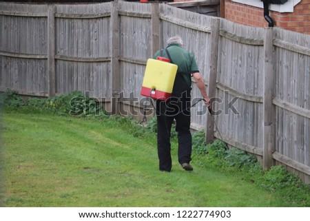 Gentleman using weed killer hazard liquid to kill weeds in a field .back pack holds liquid