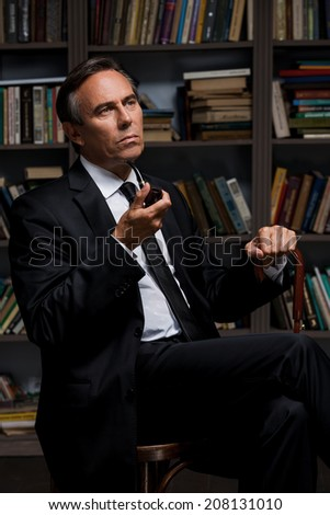 Gentleman with pipe. Thoughtful mature man in formalwear holding pipe and cane while sitting against bookshelf