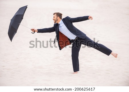 Gentleman with umbrella. Playful young man in formalwear holding umbrella while standing in desert