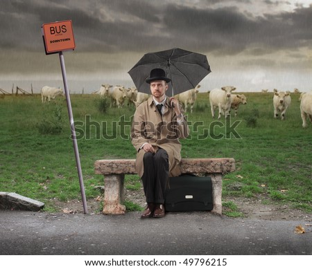 Gentleman with umbrella sitting on a bench and waiting for a bus