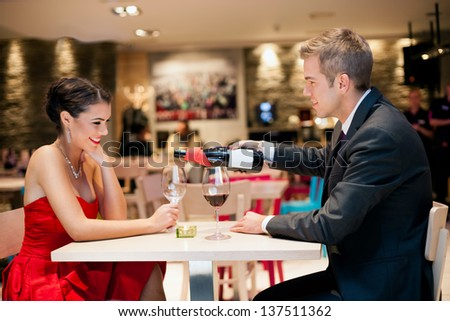 Gentlemen poured wine into a wine glass at a romantic dating