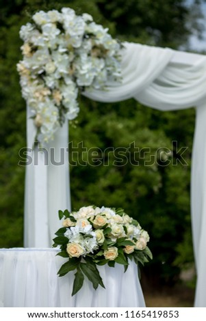 gently white wedding ceremony on a background of greenery #1165419853