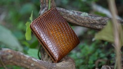 genuine cowhide men's wallet article brush off handmade with crocodile skin motif among the branches of wild trees in the backyard garden