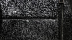 Genuine leather with a sewn-in zipper, brown genuine leather. Leather texture close-up.