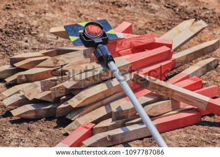 Geodesic prism over pile of red painted wooden survey pegs