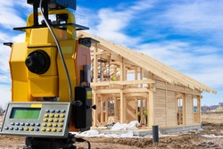 Geodesy. Total station next to buildings under construction. Equipment  geodesy works. Concept - work surveyor. Services of surveyor. Total station is directed to building frame. Frame wooden house