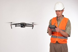 Geodesy using a drone. Surveyor in a white construction helmet. The surveyor launched the quadrocopter. A man watches the flight of a quadrocopter. The survey areas with the aid of drones.