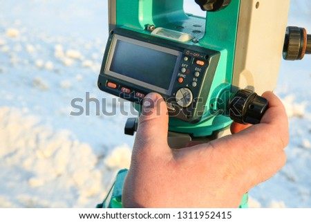 geodetic equipment is ready to work. the surveyor takes measurements. the hand of the surveyor sets up equipment for operation. surveyor's finger presses the button on the total station.