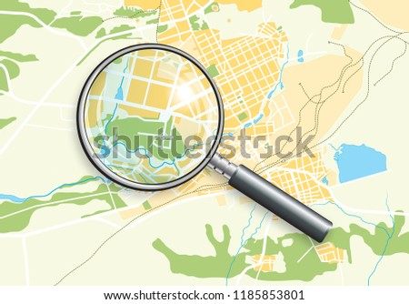 Stock Photo Geographic Map of the City with a Magnifying Glass; Cartography Chart and A Lens.