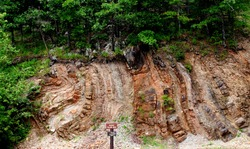 Geographic shows earth fold due to earth movement in rock stratum. Folding of rock layers bend in rock strata in the side of this mountain near Lake Ouachita and Hot Springs National Park Arkansas.