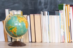 Geography lesson. A globe among a large number of school books.