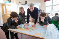 Geography teacher and middle school students using a map in the classroom.
