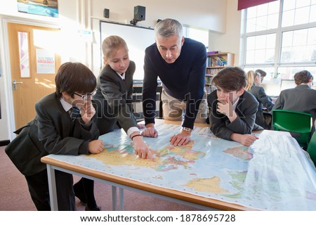 Geography teacher and middle school students using a map in the classroom. Stock foto ©