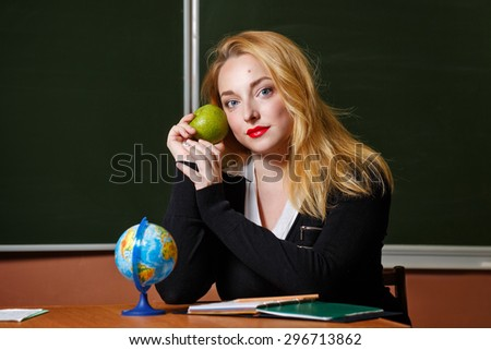 Geography teacher sitting at her desk. A girl holding a green apple. Back to school.
