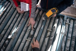 geological gold core samples with team of mining  workers measuring drilled rock top view