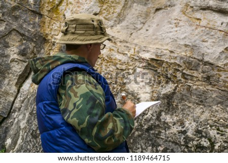 geologist conducts a description of the rocky outcrop during surface geological survey work #1189464715