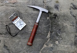 Geologists compass on the stones with hammer. Geology science concept. The geologist's hammer and tools are laid out on a stone while filedwork