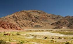 Geology. The Andes mountain range. Panorama view of the mountains, yellow grass and valley, under a deep blue sky.