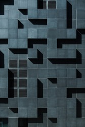 Geometric architecture detail of black modern building. Playful facade with optical illusion. Abstract background.