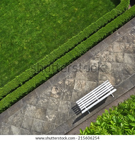 Geometric background with a white bench in a green park. Top view