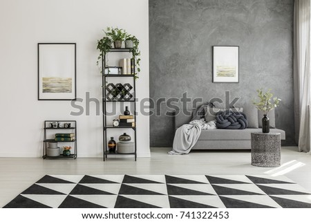 Geometric, black and white carpet in monochromatic living room interior with metal coffee table and gray sofa #741322453