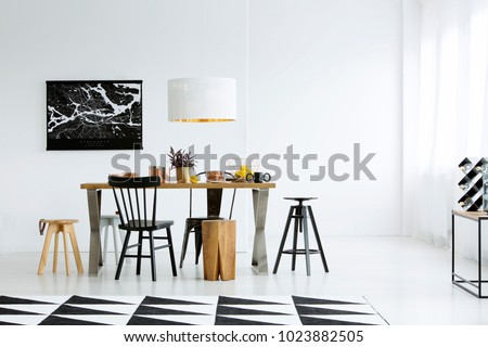 Geometric carpet and black chairs at dining table in bright dining room interior with dark poster on white wall #1023882505
