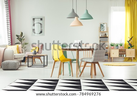 Geometric carpet in cozy living room interior with pastel lamps above wooden table and yellow, mint and grey chair against a wall with poster