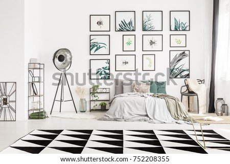 Geometric carpet in monochromatic bedroom with metal lamp and chair next to king-size bed #752208355