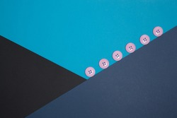 Geometric composition with pink buttons. Black, blue, blue paper. Crossing flowers. Classic colors. Business style.