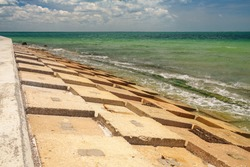 Geometric concrete revetment between low seawall and the Gulf of Mexico at the edge of a county park in west central Florida, for coastal and environmental themes
