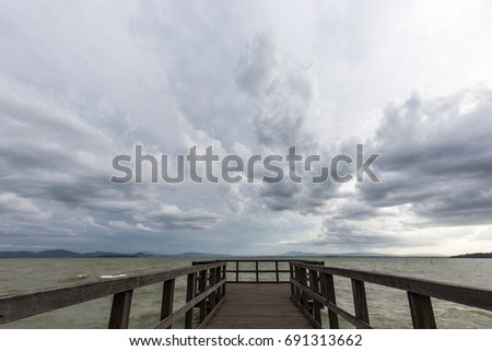 Geometric, first person view of a pier on a lake, beneath an overcast, moody sky #691313662