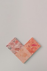 Geometric heart arrangement. Pink terrazzo tiles against light grey background. Minimal flat lay love concept.