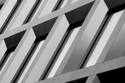 Geometric pattern from part of building facade. Modern architecture of commercial building walls and windows made of glass. Abstract architecture background.