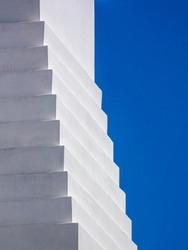 Geometric steplike detail of whitewashed concrete building in the minimalist architectural style of New Urbanism in a beach town on a sunny morning along the Gulf Coast of Florida