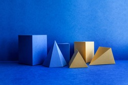 Geometrical figures still life composition. Three-dimensional blue yellow prism pyramid tetrahedron rectangular cube objects on blue background. Platonic solids figures, simplicity concept photography