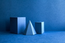 Geometrical figures still life composition. Three-dimensional prism pyramid tetrahedron rectangular cube objects on blue background. Platonic solids figures, simplicity concept photography.