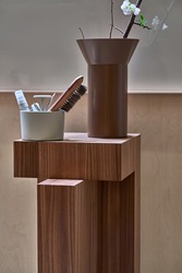 Geometrical textured wooden stand with a light holder with a brush and pencils and a marker pen, brown vase with a blossom plant in the illuminated interior. Closeup vertical photo.