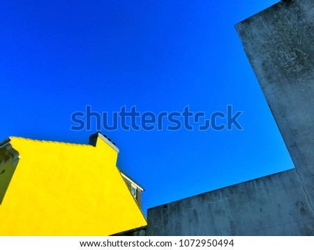 Geometry bstract of lines shapes and colours from top part of a yellow house, concrete wall and blue sky. Urban abstract, natural architectural abstract. Natural Background and pattern
