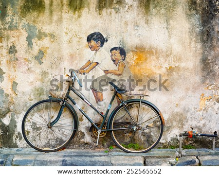 GEORGE TOWN PENANG MALAYSIA CIRCA JUL 2014 Public art in Malaysia uses contrasting media of sculpture and painting for this mural of two girls riding a bicycle
